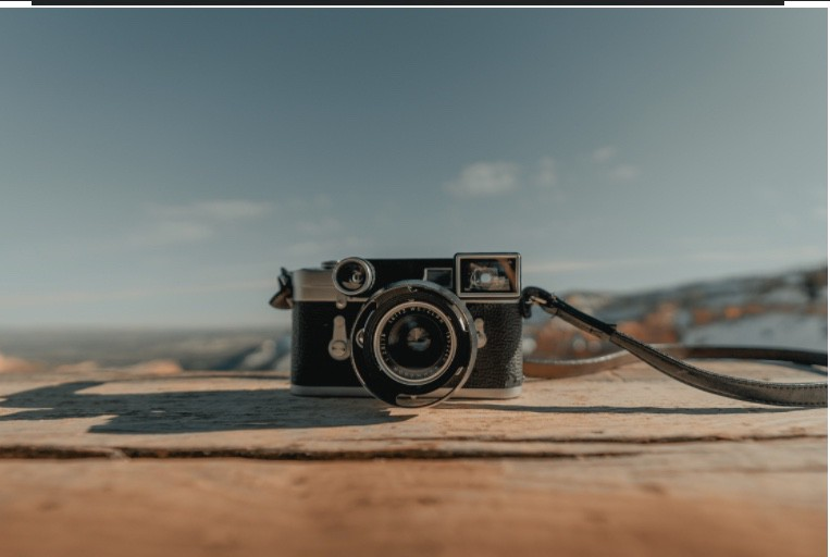 A camera on a ledge with the sky in the background.