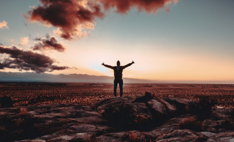 An image of a man standing on a rock with arms outspread in front of a sunset.