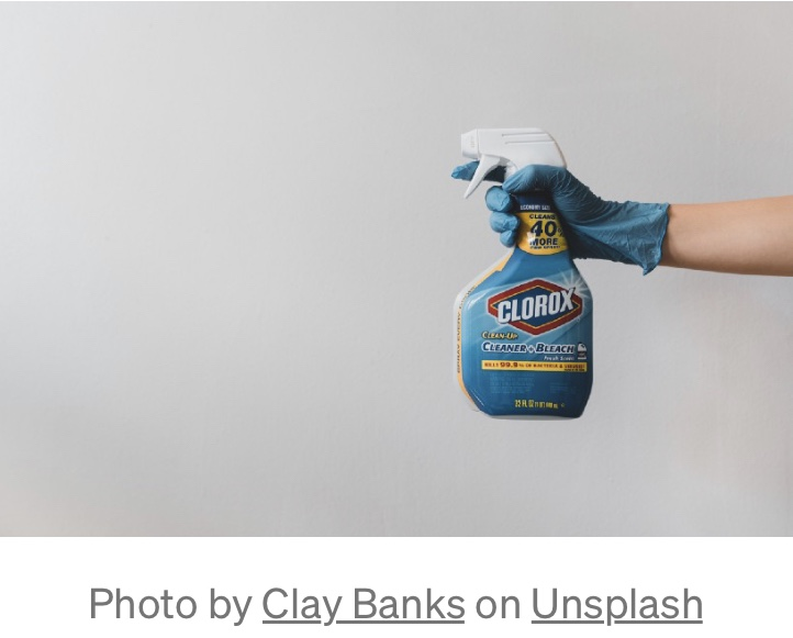 A woman points her clorox bleach cleaner at dirt and grime.